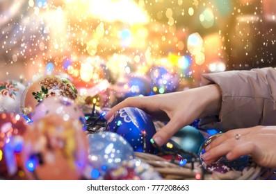 Sale at the Christmas market - girl chooses Christmas balls close-up