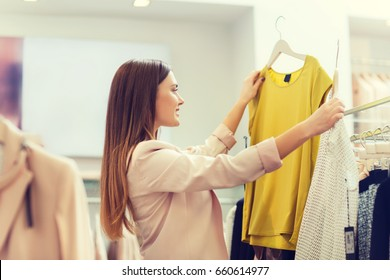 sale, clothes , shopping, fashion and people concept - happy young woman choosing between two shirts in mall or clothing store