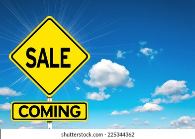 Sale coming sign yellow road sign with clouds and sky in background