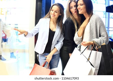 sale, consumerism and people concept - happy surprised young women with shopping bags pointing finger to shop window in the mall