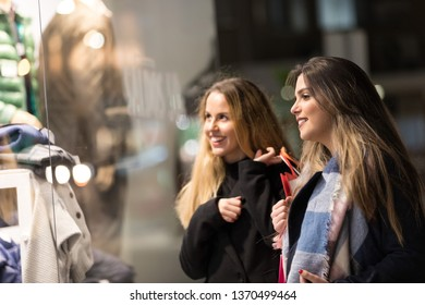 sale, consumerism and people concept - happy young women with shopping bags walking along city street