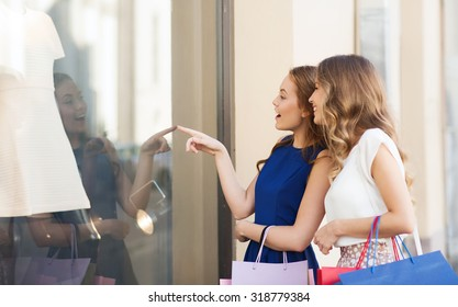 sale, consumerism and people concept - happy surprised young women with shopping bags pointing finger to shop window outdoors