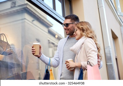 sale, consumerism and people concept - happy couple with shopping bags and coffee paper cups looking at shop window in city