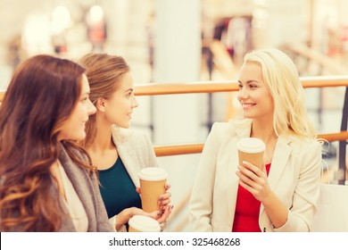 sale, consumerism and people concept - happy young women with shopping bags and coffee paper cups in mall