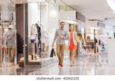 e306ee6397 sale, consumerism and people concept - happy young couple with shopping  bags walking in mall