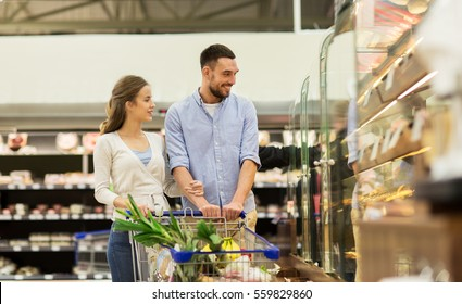 sale, consumerism and people concept - happy couple with food in shopping cart at grocery store or supermarket