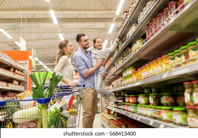 sale, consumerism and people concept - happy family with child and shopping cart buying food at grocery store or supermarket