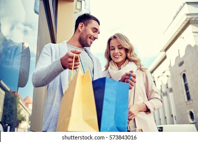 sale, consumerism and people concept - happy couple looking into shopping bag at shop window in city