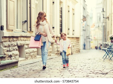 sale, consumerism and people concept - happy mother and child with shopping bags walking along city street