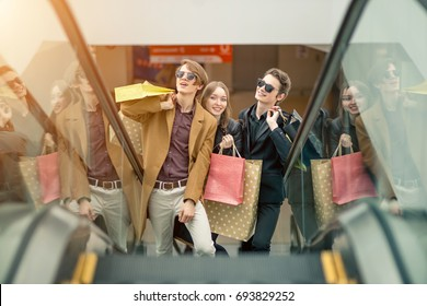 sale, consumerism and people concept - happy young couple with shopping bags going down by escalator and pointing finger in mall