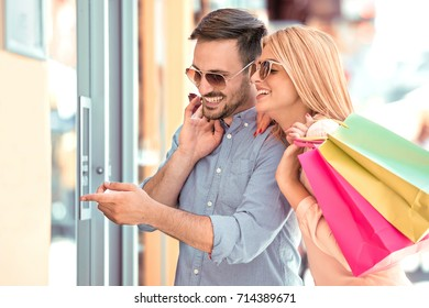 Sale, consumerism and people concept - happy couple with shopping bags  looking at shop window in city.