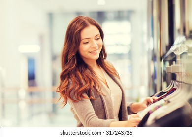 sale, consumerism, shopping and people concept - happy young woman choosing clothes in mall