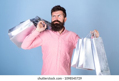 Sale and discount concept. Guy shopping on sales season with discounts. Hipster on strict face shopping addicted or shopaholic. Man with beard and mustache carry shopping bags, light blue background