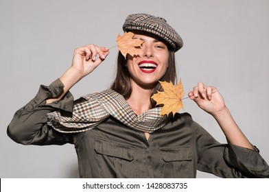 Sale for entire autumn collection, incredible discounts and wonderful choice. Surprise woman playing with leaves and looking at camera. Autumn girl preparing for Autumn sale. Autumn concept