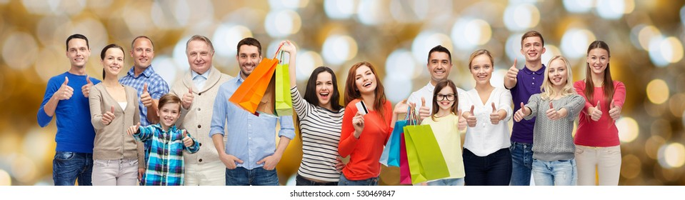 sale, family, generation and people concept - group of happy men and women with shopping bags and credit card showing thumbs up over holidays lights background