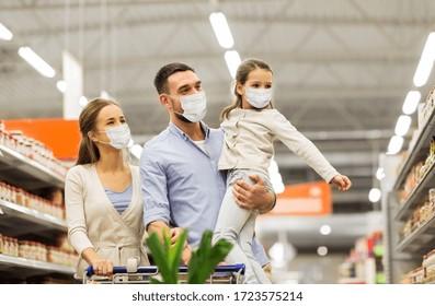 Verkauf, Familie und Pandemie Konzept - glückliche Mutter, Vater und kleine Tochter tragen Gesichtsschutzmasken für den Schutz vor Viruserkrankungen mit Einkaufswagen, die Lebensmittel im Supermarkt kaufen