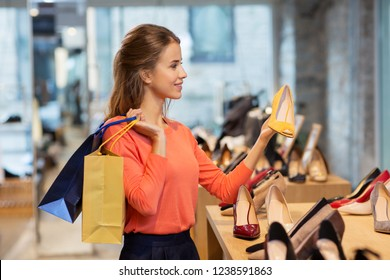 sale, fashion and people concept - happy young woman with shopping bags choosing shoes at store