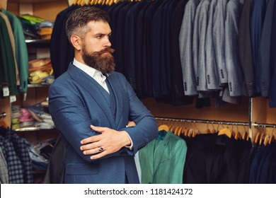 sale, fashion, retail, business style and people concept - seriously hipster man with beard at clothing store. Modern young handsome businessman dressed in classical suit while standing in suit shop