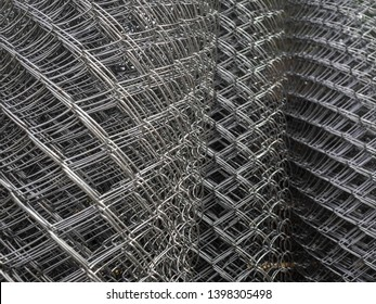 Sale of fencing, rolled into rolls. Galvanized steel grating in stock. Fence with large cells. Texture, background