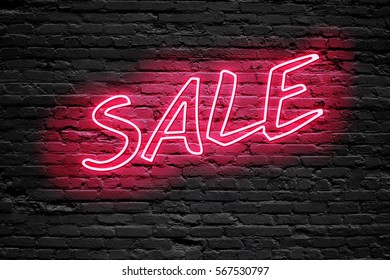 SALE. fluorescent Neon tube Sign on dark brick wall. Front view. Can be used for online banner ads or background. night moment.