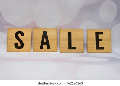 sale lettering written in wooden tiles with blurred stylish grey bubble background.