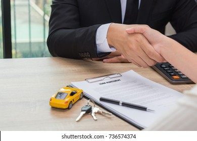 Sale man or businessman shaking hands with female after car loan agreement was signed.