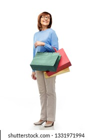 sale and old people concept - smiling senior woman in glasses with shopping bags over white background