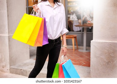 sale and people concept smiling young woman with shopping bags having fun with their purchases In the shopping mall