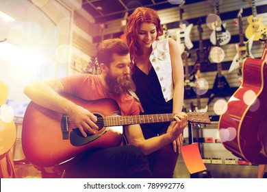 sale, people and musical instruments concept - happy couple of musicians playing guitar at music store over lights