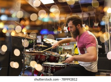 sale, people, musical instruments and entertainment concept - male musician playing cymbals on drum kit at music store or studio over lights