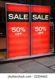 Sale posters in a shop window advertising 50% discount