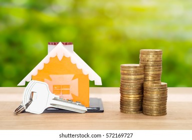 Sale and rental properties loans for real estate concept. Model home with key and coins.