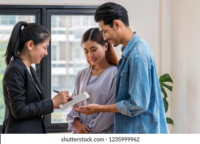 Sale representative offer the estate price list and condition for contact purchase or rental via technology tablet when walkin in new place,Moving and House Hunting concept