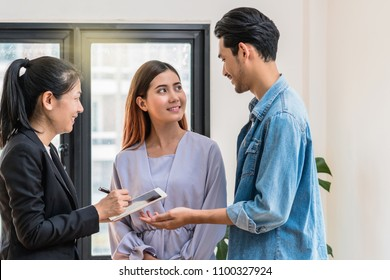 Sale representative offer the house price list and condition for house purchase or rental via technology tablet when walkin in new house,Moving and House Hunting concept