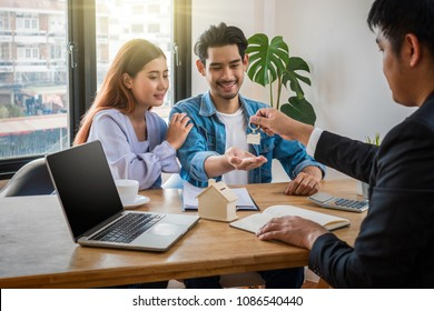 Sale representative offer the key chain to Asian young couple after signed contact house purchase or rental on the working space table in new place,Moving and House Hunting concept