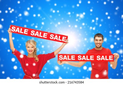 sale, shopping, christmas, holidays and people concept - smiling man and woman in red clothes with sale signs over blue snowy background