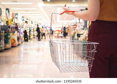 sale, shopping, consumerism and people concept - woman with food basket in supermarket