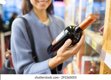 sale, shopping, consumerism and people concept - happy young woman choosing and buying wine in market or liquor store