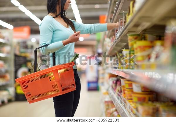 venta, compras, consumismo y concepto de personas - mujer con cesta de alimentos en tienda o supermercado