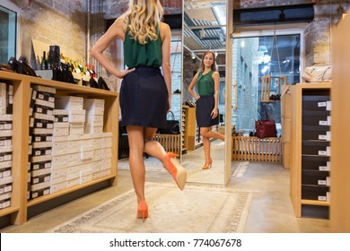 sale, shopping, fashion and people concept - young woman in high-heeled shoes posing at store mirror
