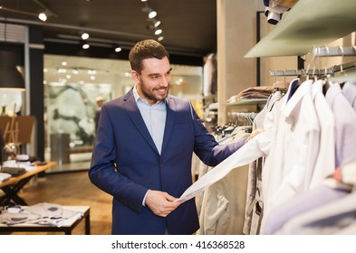 sale, shopping, fashion, style and people concept - happy young man in suit choosing shirt in mall or clothing store