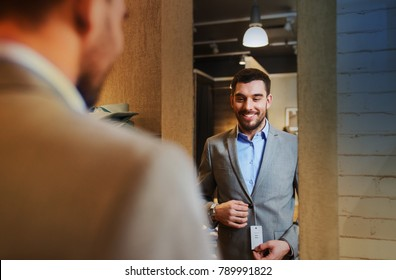 sale, shopping, fashion, style and people concept - young man choosing and trying jacket or suit on and looking to mirror in mall or clothing store