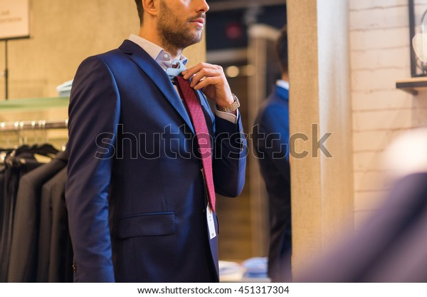 sale, shopping, fashion, style and people concept - elegant young man choosing and trying tie on at clothing store