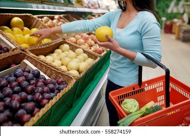 sale, shopping, food, consumerism and people concept - woman with basket buying pomelo at grocery store