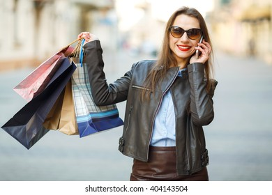 Sale, shopping, tourism and happy people concept - beautiful woman with shopping bags is talking on smart phone on a street