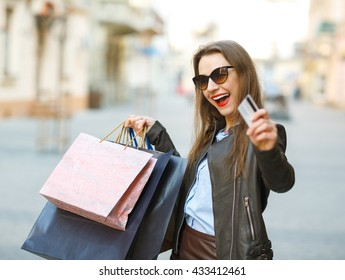 Sale, shopping, tourism and happy people concept - beautiful woman with shopping bags and credit card in the hands on a street