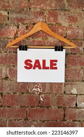 Sale sign hanging on coat hanger against rustic brick wall