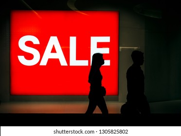 Sale sign in mall and shoppers silhouettes