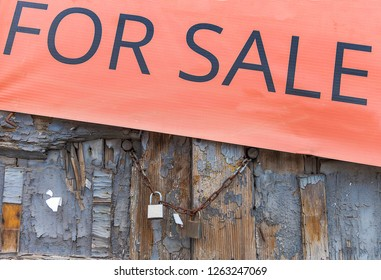 Sale sign on weathered old door secured with chain and padlock .Stock Image.