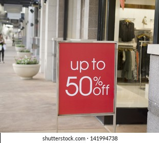 Sale sign outside fashion retail store in shopping mall